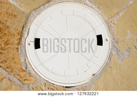 The lid to a swimming pool skimmer on flagstone.