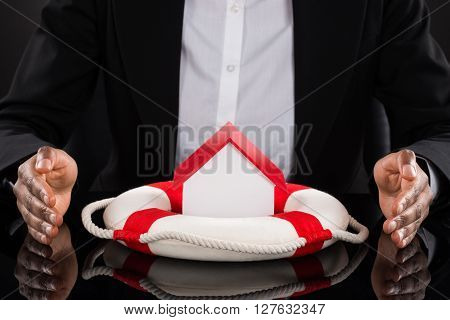 Businessperson's Hand Protecting House With Lifebelt