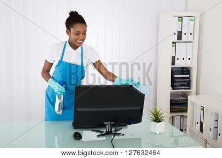 Female Janitor Cleaning Computer