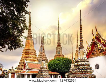 Classical Thai architecture in Wat Pho public temple at dramatic orange sunset sky Bangkok Thailand. Wat Pho known also as the Temple of the Reclining Buddha.