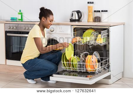 Happy Woman Arranging Plates In Dishwasher