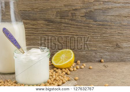Bottle Of Soy Milk, Soy Mayonnaise And Lemon With Soybeans, On Wooden Background