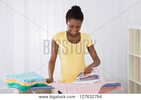Happy Woman Ironing Clothes On Iron Board