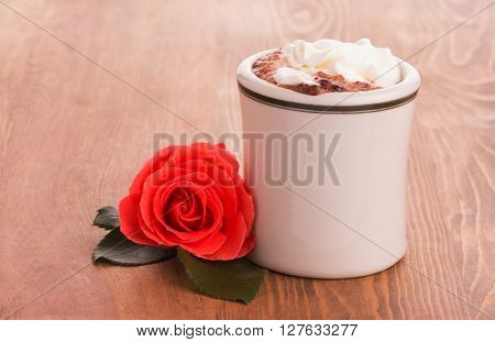 Romantic red rose with a cup of hot chocolate on wooden table - concept of a sweet gesture