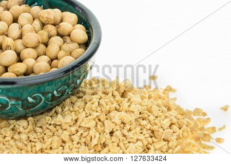 Soybeans in bowl and dry soya mince closeup on white background with copy-space
