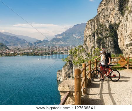 Verona, Italy - April 20, 2016: Two cyclists look the panorama from the Ponale trail in Riva del Garda Italy.