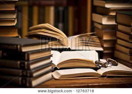 öffnete Buch, liegend in der virtuellen Bibliothek mit einer Brille