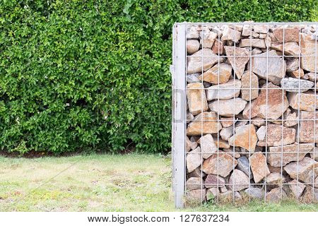 The plant hedge and rock fence in cage with high voltage post background.