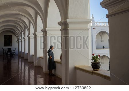 Sucre, Bolivia in September 2015: A nun looks out of a window in a convent. The convent is a beautiful colonial building in Bolivias capital