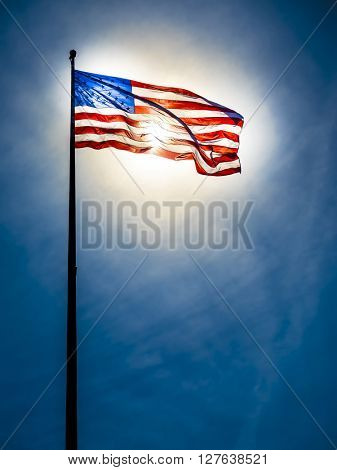 American flag on the blue sky in front of the sun, sun is shining through the flag