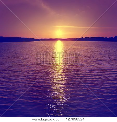 Dramatic sunset over water surface. Vintage image.