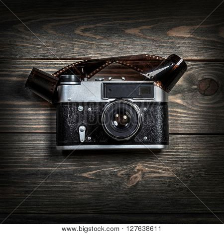 Retro film photo camera on the wooden background.