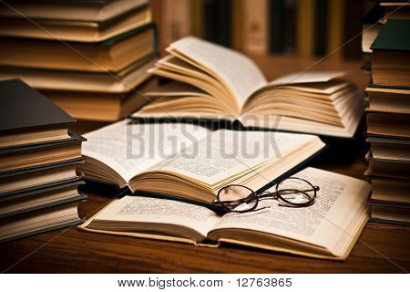 opened book, lying on the bookshelf with a glasses