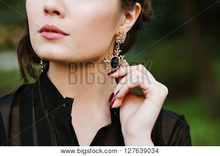 Closeup portrait of a girl brunette. A young woman touches an earring with precious stones. Gold earring with black stone inside. expensive Jewelry