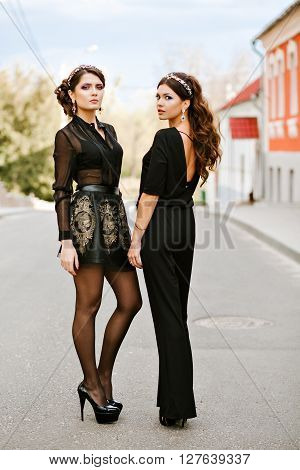 Two young beautiful fashionable woman in black clothes posing for the photographer. Headbands on the head, in the ears of stylish earrings. Expensive jewelry. curly hairstyles