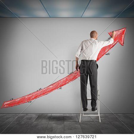 Man on a ladder draws an arrow