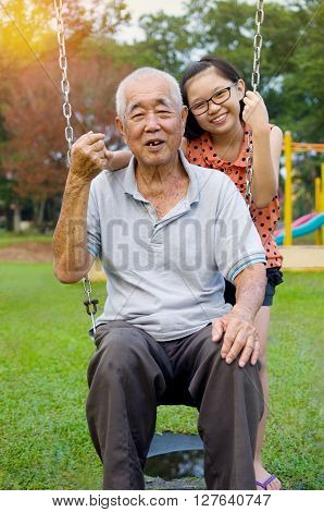 Happy Asian Grandfather posing with his grandchild
