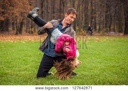 Father and daughter play in park on an autumn day.
