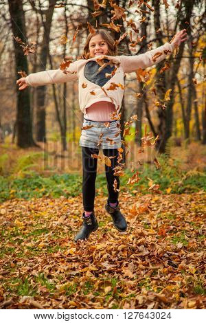 Cheerful child, with heart shaped shirt, plays with leaves in park on an autumn day.
