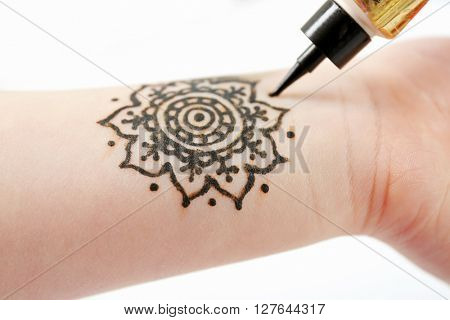 Image of henna ornament on girl's wrist closeup