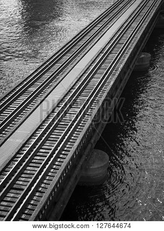 Railroad tracks over water in black and white