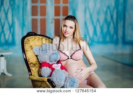 Beautiful pregnant woman in sexy nightwear sitting on armchair with teddy bear. pregnant woman in cream lingerie with white soft toy bear.