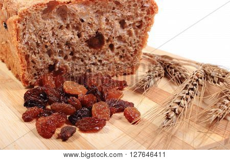Fresh baked wholemeal bread heap of raisins and ears of wheat lying on cutting board concept for healthy eating