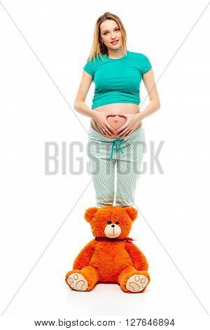 Pregnant young woman on white background making a heart on its stomach, a soft toy bear near her legs. Smiles, happy. The concept of motherhood