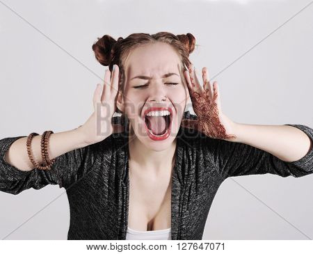 Young funny hipster woman showing tongue, shouting and surprise with funny emotion face.
