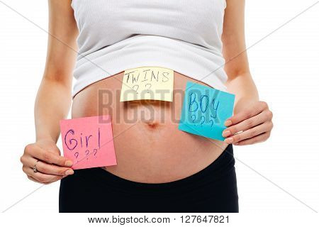 pregnant belly boy girl twins pictures on stickers, woman expecting baby, family parenting concept. young pregnant woman with sticker and question on it boy or girl or twins concept. expectant mother.