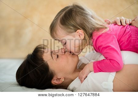 Mother with daughter kissing - lying on sofa at home