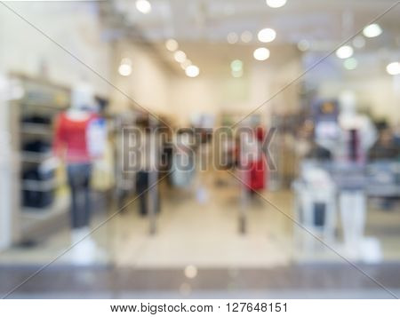 De focused or blur image of dress store with customers and dressed mannequins.