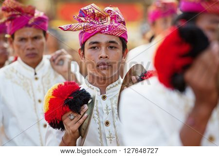 BALI INDONESIA - JUNE 13 2015: Young musician man of traditional Balinese people orchestra Gamelan in Balinese style male costume playing ethnic music on ceremony procession at Art and Culture Festival.