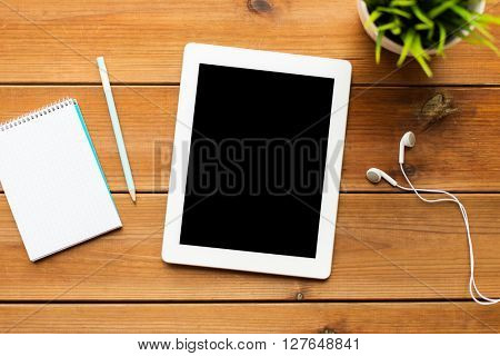education, business, people and technology concept - close up of tablet pc computer, notebook with pencil and earphones on wooden table