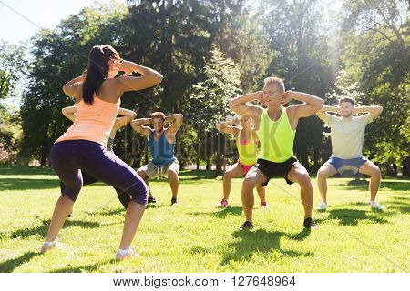 fitness, sport, friendship and healthy lifestyle concept - group of happy teenage friends or sportsmen exercising and doing squats at boot camp