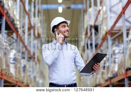 wholesale, logistic, business, export and people concept - smiling businessman with clipboard calling on smartphone at warehouse