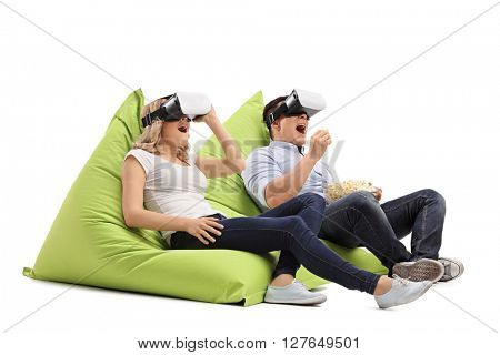 Excited young couple experiencing virtual reality seated on beanbags isolated on white background