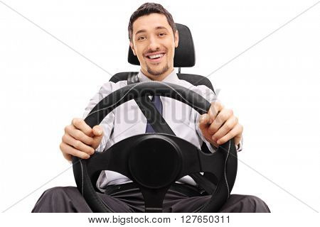 Cheerful guy holding a steering wheel seated on a car seat isolated on white background