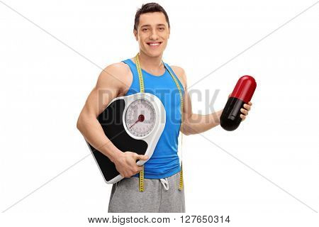 Cheerful guy holding a huge pill and a weight scale isolated on white background