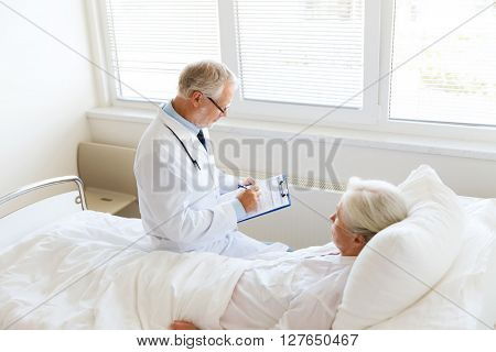 medicine, age, health care and people concept - senior woman and doctor writing to clipboard at hospital ward