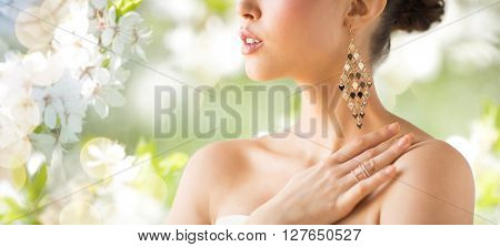 glamour, beauty, jewelry and luxury concept - close up of beautiful woman with earrings over natural spring cherry blossom