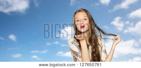 people, style, holidays, hairstyle and fashion concept - happy young woman or teen girl in fancy dress with sequins and long wavy hair sending blow kiss over blue sky and clouds background