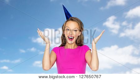 people, holidays, emotion, expression and celebration concept - happy young woman or teen girl in pink dress and party cap over blue sky and clouds background