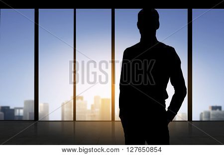 business and people concept - silhouette of business man over office window background