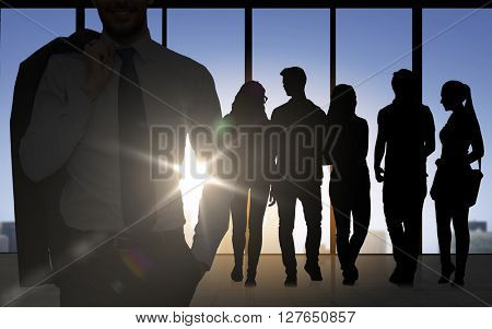 business, education and people concept - people silhouettes over office background