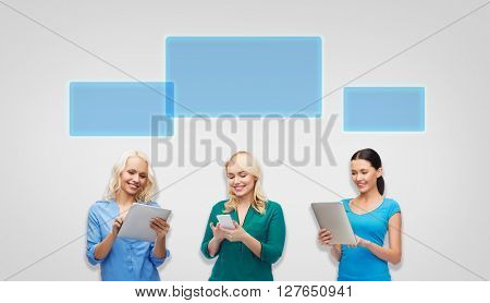 people, technology, communication and leisure concept - happy women with smartphone and tablet pc computers with empty screens over gray background