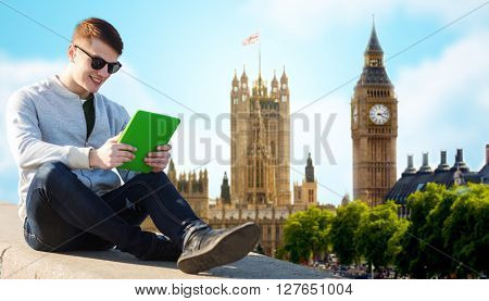 technology, travel, tourism and people concept - smiling young man or teenage boy with tablet pc computers over london city and big ben tower background