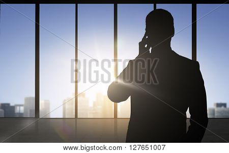 business and people concept - silhouette of businessman calling on smartphone over office window background