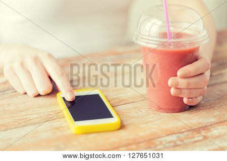 healthy eating, diet, technology and people concept - close up of woman with smartphone and cup of smoothie sitting at table