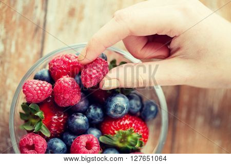 healthy eating, dieting, vegetarian food and people concept - close up of woman hands with berries mix in glass bowl on wooden table